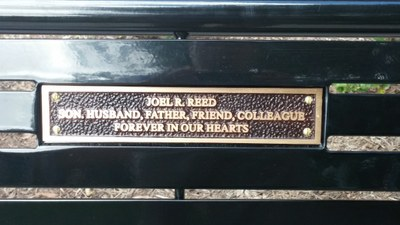 Plaque on Joel's bench that reads: Joel R. Reed; Son, husband, father, friend, colleague; forever in our hearts