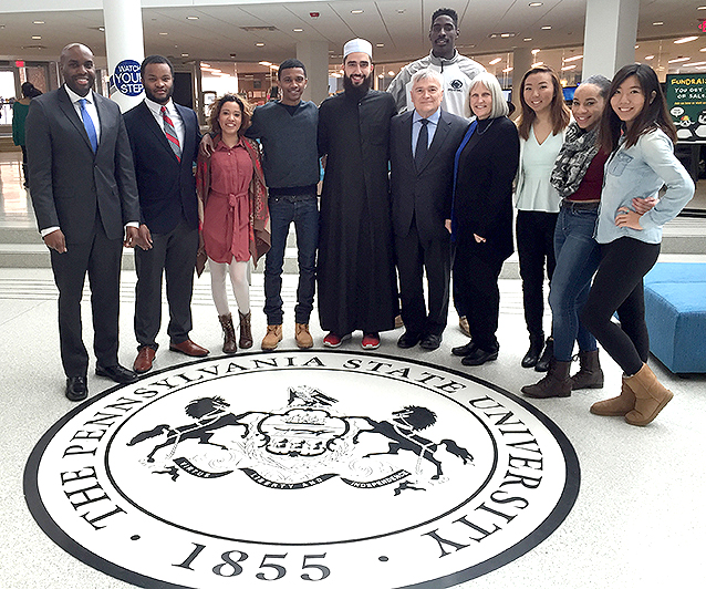 Group photo of President Barron, students, and Dr. Whitehurst in the HUB standing on the Penn State Seal