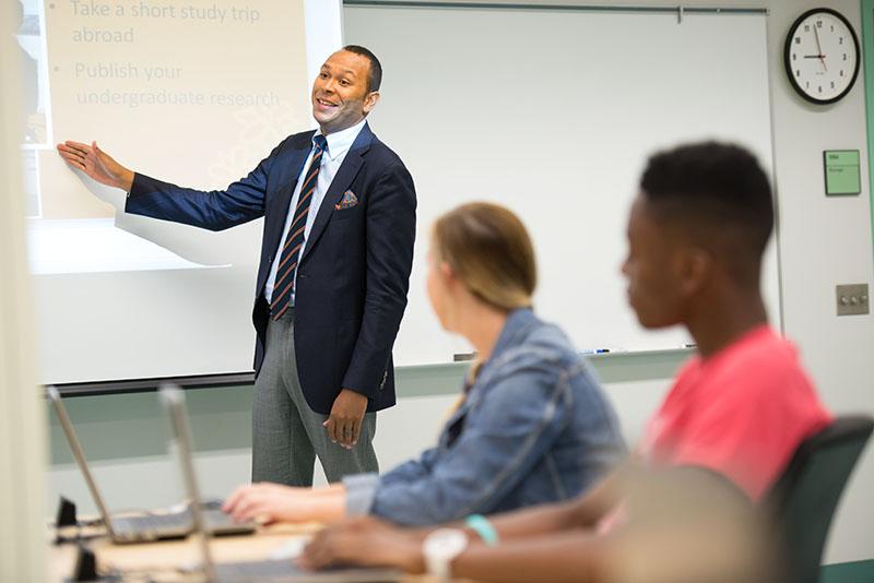 A man teaches a class using PowerPoint.
